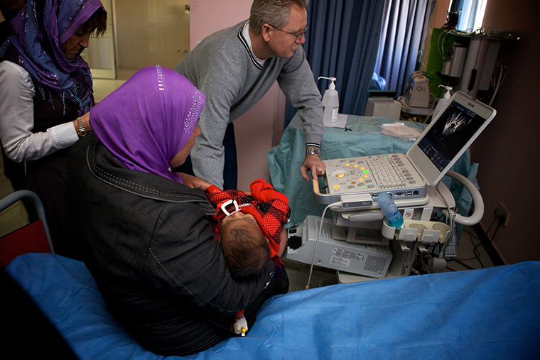 Dr. Kirk examines the echocardiogram of a baby sick with a heart defect in Fallujah, Iraq.
