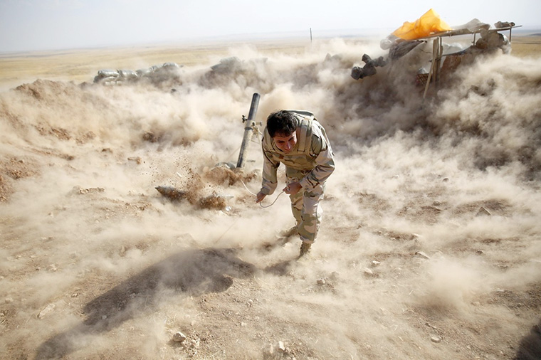Soldier fires weapon; dust cloud rises around him