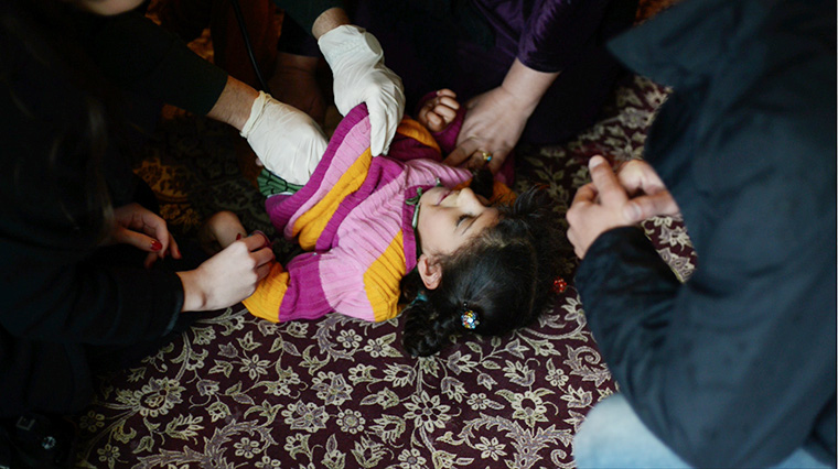 Young Hanin is surrounded by family, as she's examined by the doctor.
