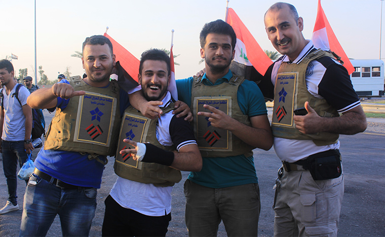 Staff from Preemptive Love Coalition and our partners Iraq Health Aid Organization pose wearing flak jackets, before departing for an emergency food drop in the besieged city of Haditha, Iraq.