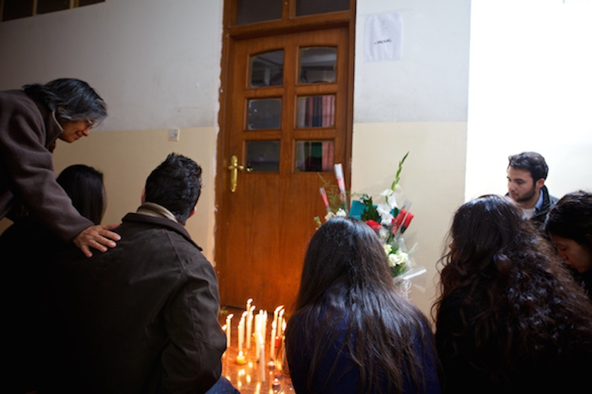 A photo of students gathered at Jeremiah Small's classroom to light candles and lay flowers.
