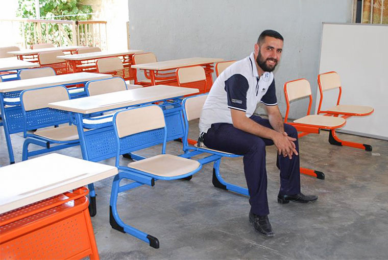 Staff from our partner organization Iraq Health Aid Organization takes a break after assembling desks.