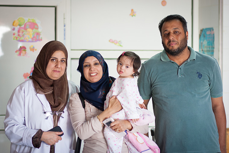 Little Malak, her cardiologist, and parents stop for a photo as Malak is discharged from hospital.