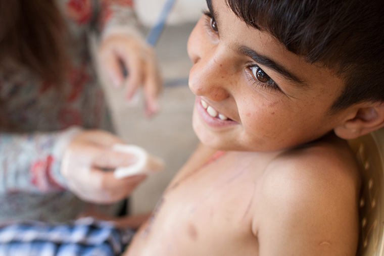 Mohammad smiles while his bandages are changed, following lifesaving heart surgery via Preemptive Love Coalition