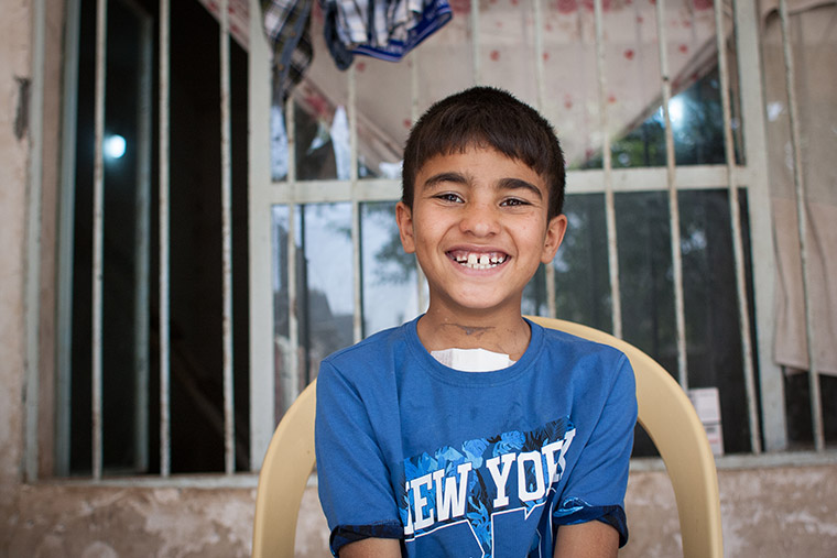 Mohammad sits in a chair in front of his house, beaming a huge smile. A fresh bandage peeks out of the top of his shirt. Mohammad recently had lifesaving heart surgery via Preemptive Love Coalition.