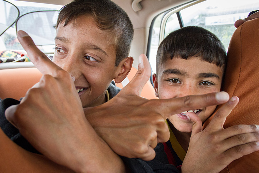 Young Mohammad and his fellow heart patient Ali ride in taxi to the airport.