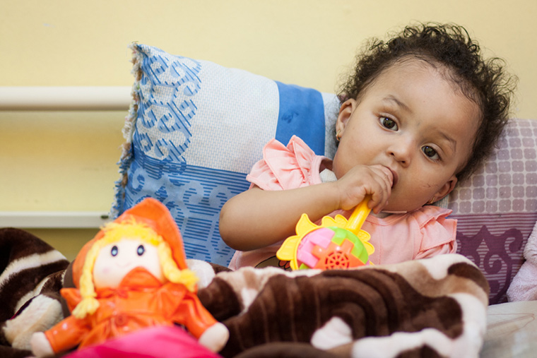 Tasnim sat on her bed, chewing the handle of her rattle, passing time until she was finally discharged from hospital following her lifesaving heart surgery.