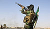 A fighter from the Shiite Badr Brigade militia wears a religious flag as he fires in the air at a checkpoint seized from Islamtic State militants outside the town of Amerli, Sept. 5, 2014.  Read more: http://www.al-monitor.com/pulse/originals/2015/01/iran-iraq-saraya-al-khorasani.html#ixzz3QP5Hvi6k