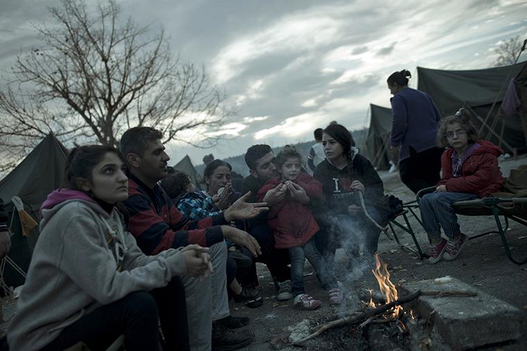 Syrian refugees, huddled around a campfire, face a bleak winter.