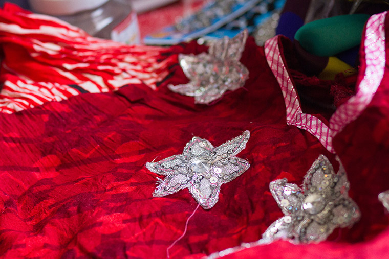 Adding hand-sewn embellishments to a hand-made dress.
