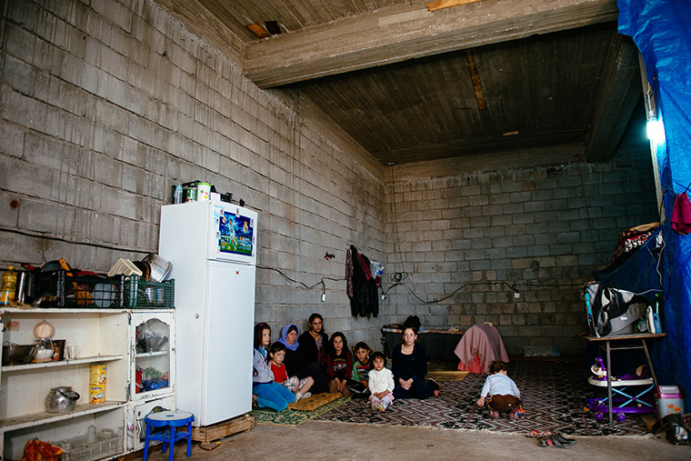 A Yazidi family, IDPs in Iraq, sit inside their temporary home—an unfinished concrete warehouse