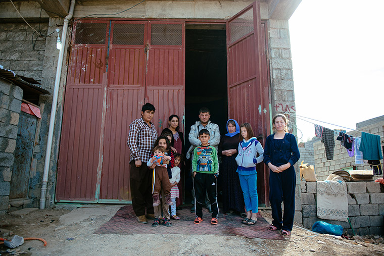 Yazidi families stand outside their temporary home in a storage warehouse