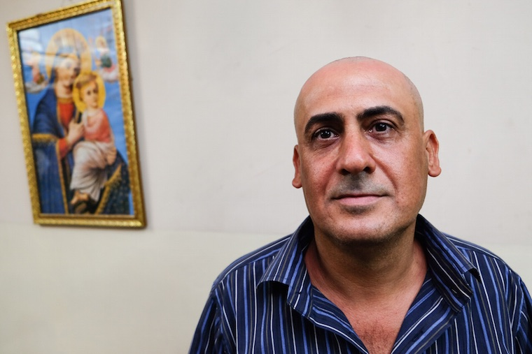 a portrait of Isaac, an Iraqi Christian man from Baghdad