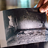 Someone holding a print photograph of a house destroyed by ISIS violence.