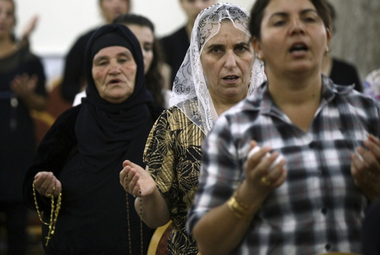 Iraqi Christians fleeing the violence in the Iraqi city of Mosul, pray at the Mar Afram church at the town of Qaraqush in the province of Nineveh