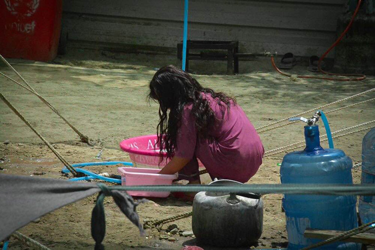 A young girl cleans up after a meal using plastic bins recently given to her family, displaced from Ramadi in Iraq.