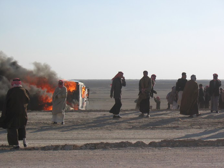 A car burns on the side of the road in Iraq, during the US invasion.