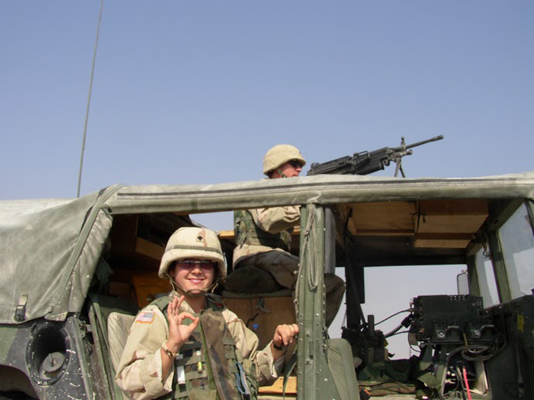 In uniform, Diana takes a minute to smile beside a military vehicle.