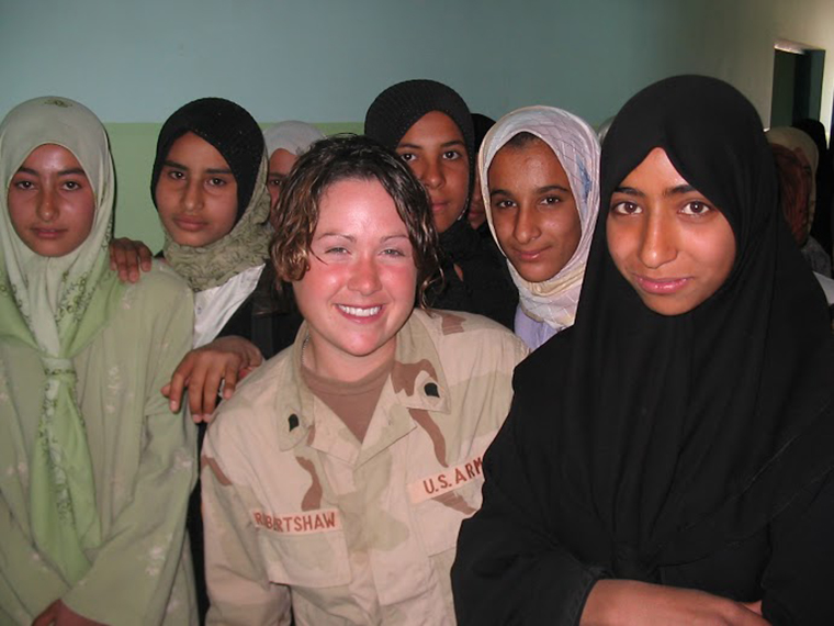 Diana Oestreich was part of the US forces in Iraq during the US invasion. In this photo she stands with a group of local Iraqi women.