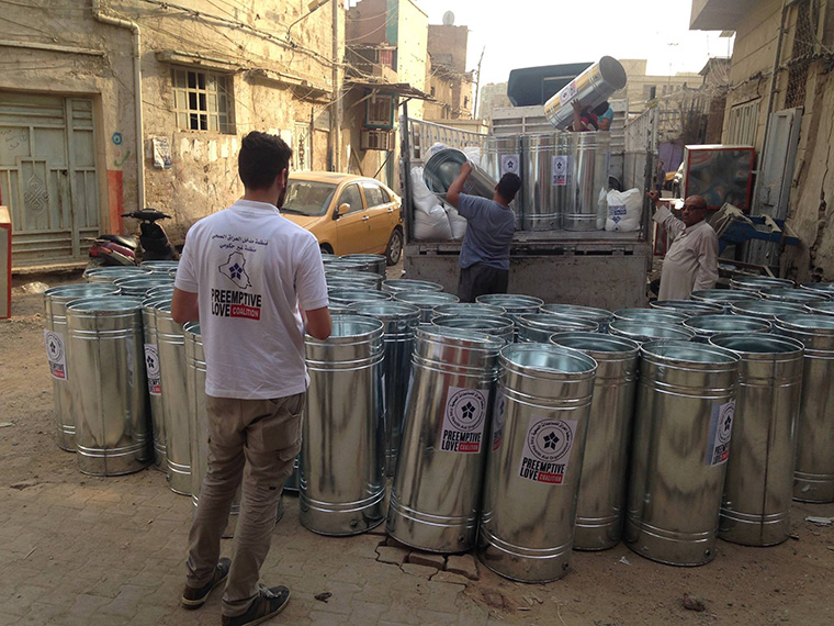 Water tanks being loaded onto a truck, to be delivered to Iraqi families trying to rebuild their lives.