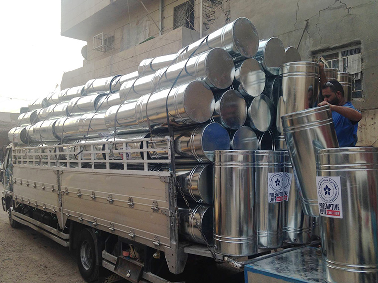 A truck loaded high with water tanks, destined for formerly displaced Iraqi families.