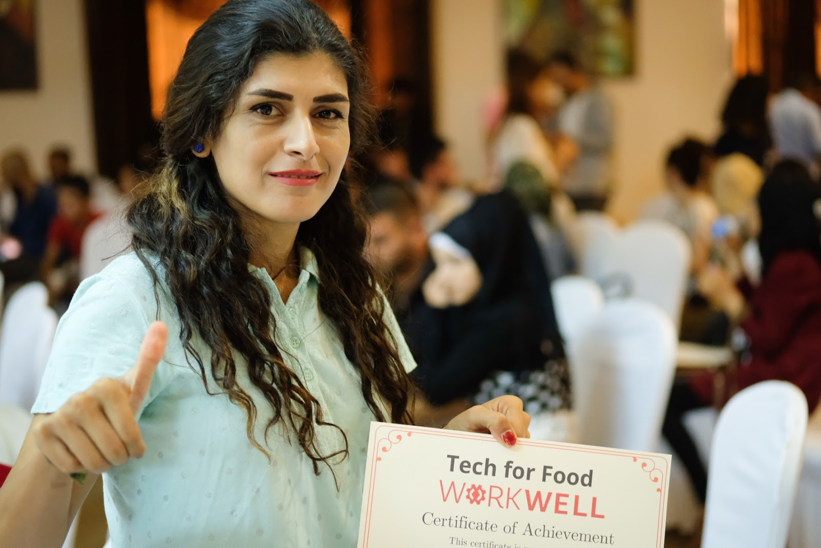 woman holding WorkWell certificate